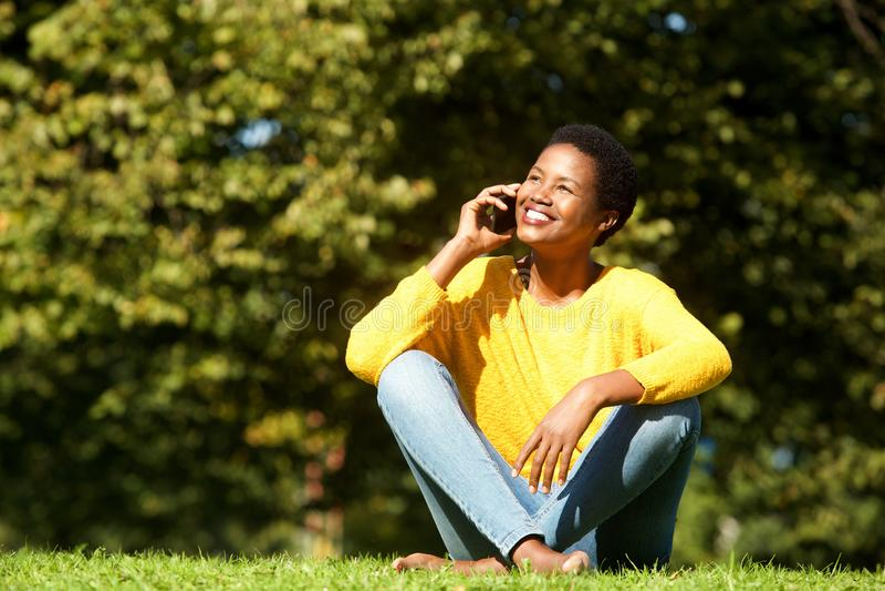 Mulher negra nova que fala no telefone celular no parque foto de stock royalty free