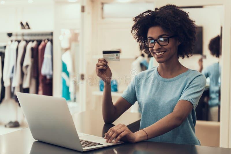 Mulher negra nova que guarda o cartão de crédito na loja fotos de stock