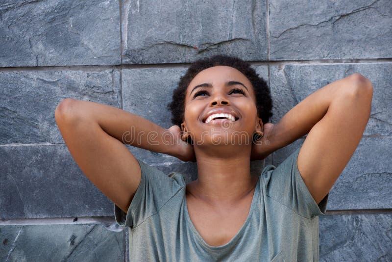 Mulher negra nova que ri contra a parede cinzenta com mãos atrás da cabeça imagens de stock royalty free