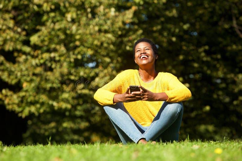 Mulher negra nova que senta-se no parque com telefone celular foto de stock