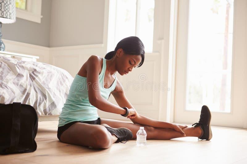 Mulher negra nova que usa o relógio esperto ao exercitar em casa imagens de stock