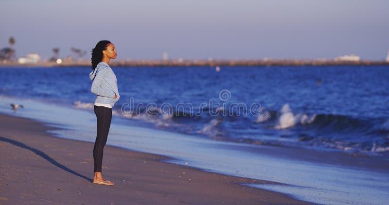 A mulher negra que aprecia a vista para o mar até ondas vem fotografia de stock royalty free