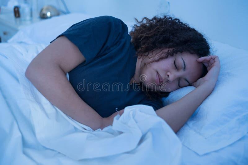 Mulher negra que encontra-se na cama que tenta dormir fotografia de stock