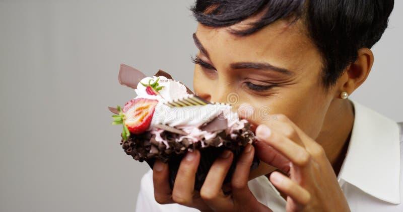 Mulher negra que faz uma confusão que come uma sobremesa extravagante enorme foto de stock