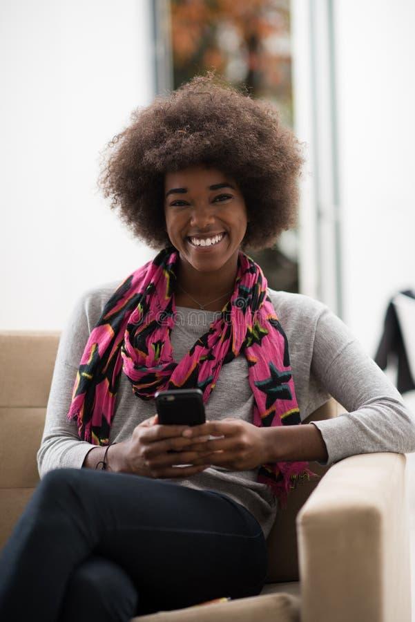 Mulher negra que senta-se no sofá e que usa o telefone celular fotografia de stock royalty free