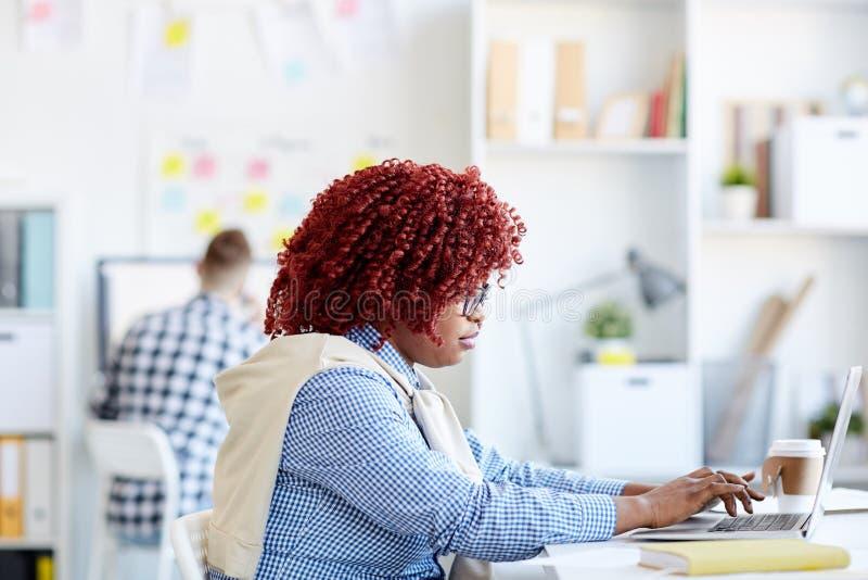 Mulher negra que trabalha no escritório foto de stock