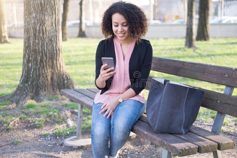 Mulher negra que usa o app no telefone celular fotografia de stock