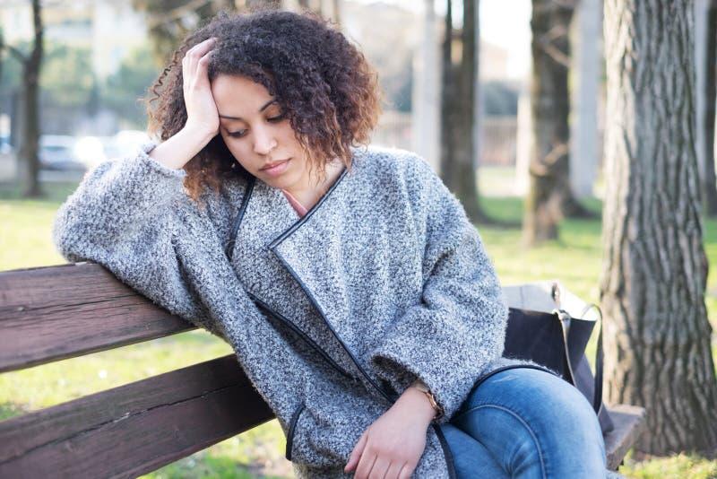 Mulher negra triste assentada apenas em um banco fotografia de stock royalty free