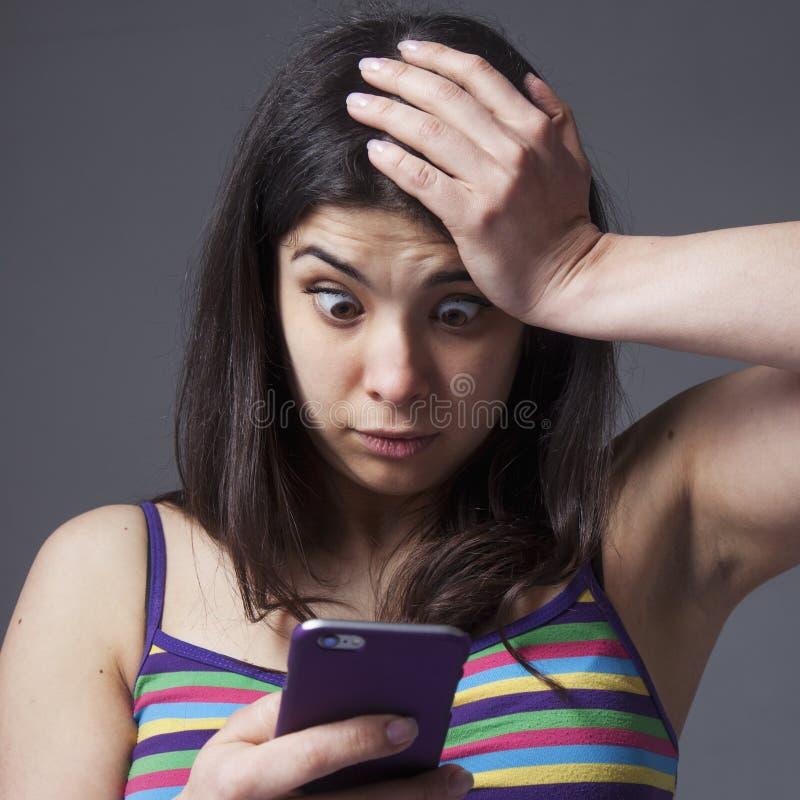 Mulher nervosa que jura em seu telefone celular As más notícias, nega imagem de stock royalty free
