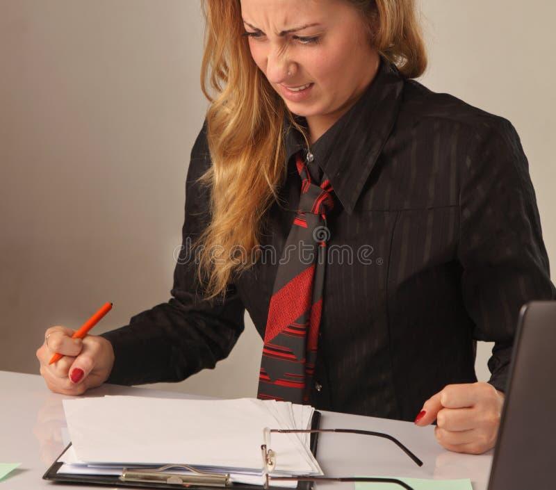 Mulher nervosa que trabalha com originais retrato psicológico, AG imagem de stock