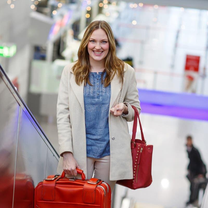 Mulher no aeroporto internacional, na escada rolante no terminal da chegada fotos de stock