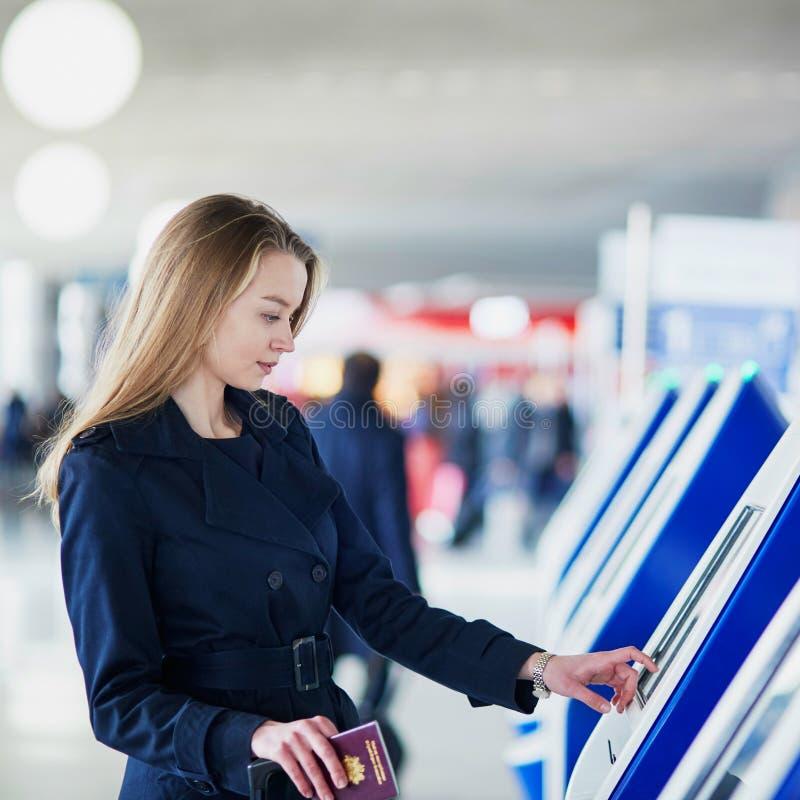Mulher no aeroporto internacional que faz o auto - verificação - dentro imagens de stock