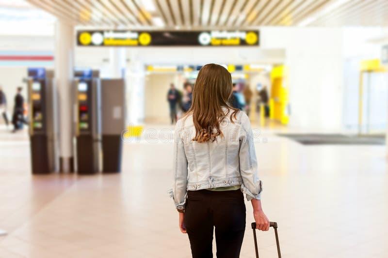 Mulher no aeroporto, levando seu saco do trole fotografia de stock