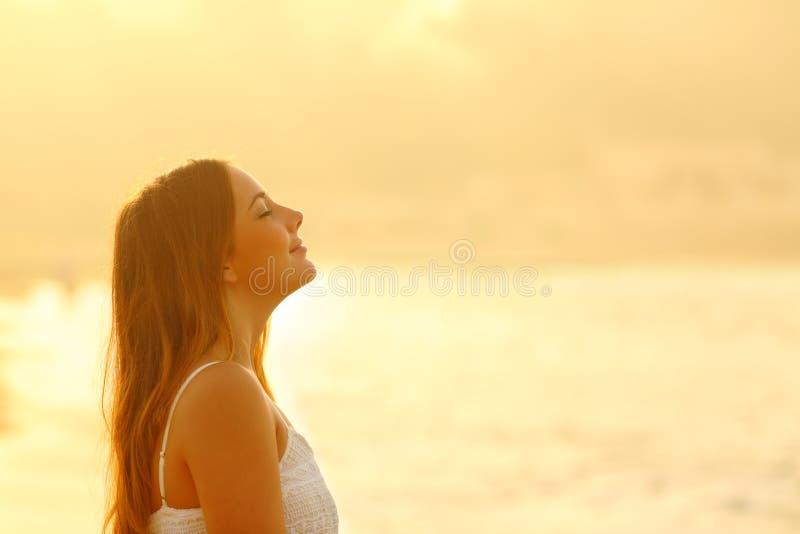 Mulher no ar fresco de respiração de relaxamento do por do sol imagens de stock royalty free