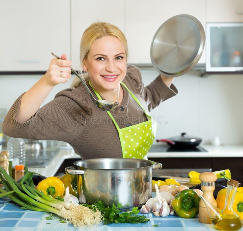 Mulher no avental na cozinha fotos de stock royalty free