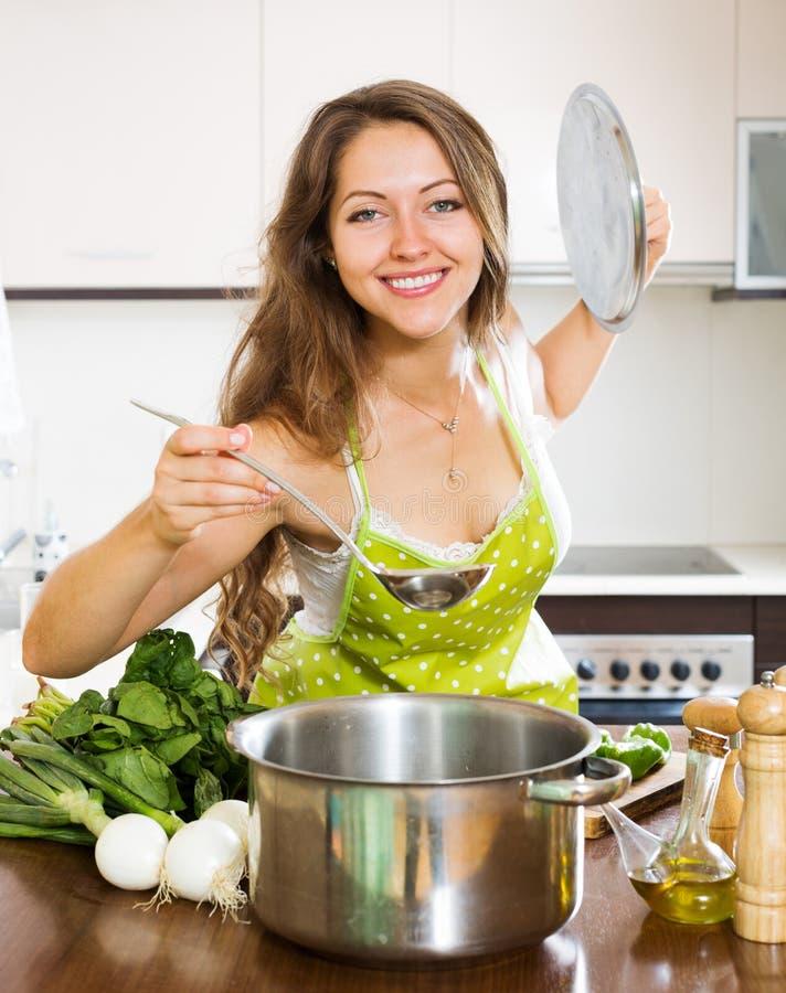 Mulher no avental que cozinha a sopa na cozinha fotografia de stock