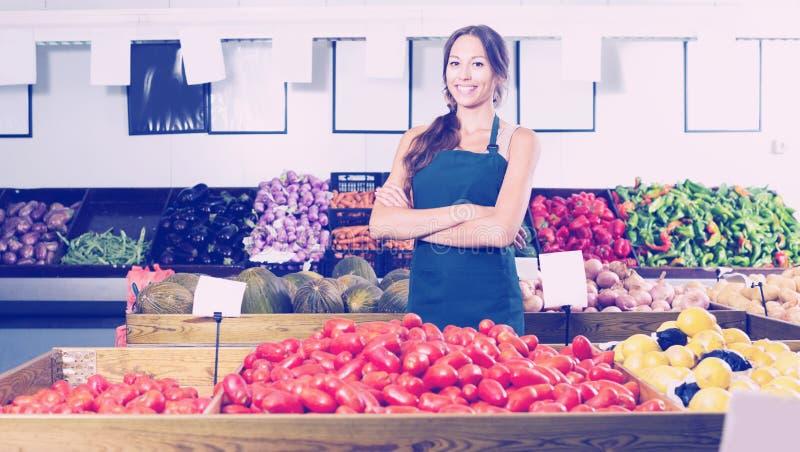 Mulher no avental que vende tomates orgânicos na loja foto de stock