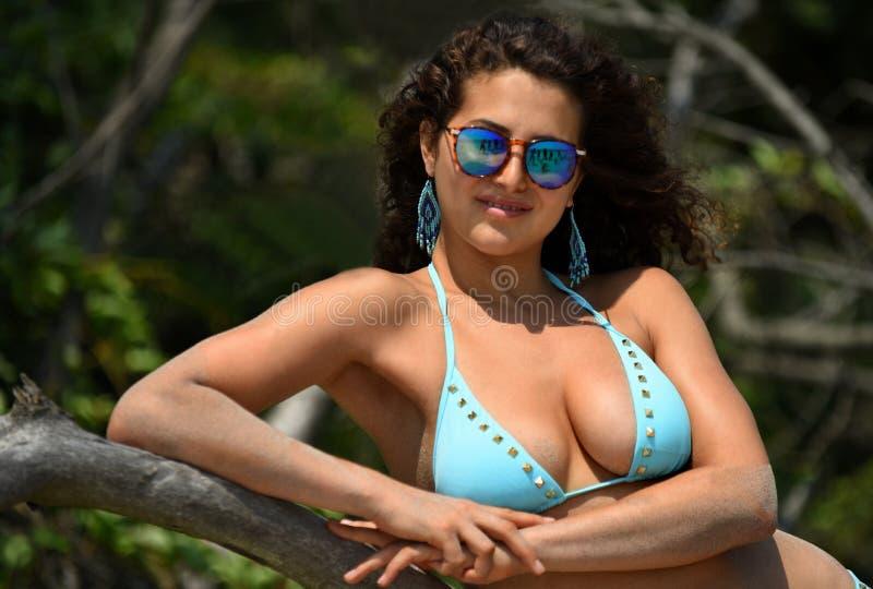 Mulher no biquini azul e nos óculos de sol que levantam na praia fotos de stock