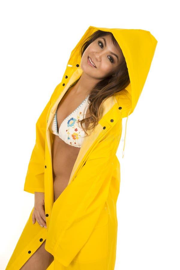 Mulher no biquini branco no olhar amarelo do lado do revestimento de chuva imagens de stock royalty free