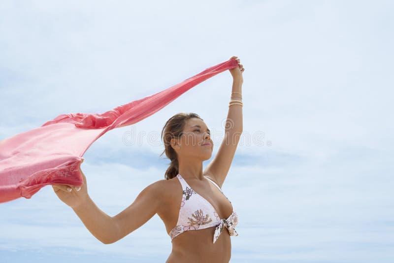 Mulher no biquini com as mãos levantadas guardando o lenço na praia fotos de stock royalty free