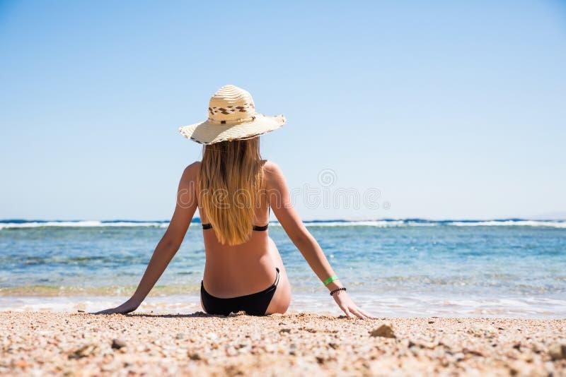 Mulher no biquini preto que descansa na praia no chapéu de palha perto do mar fotos de stock