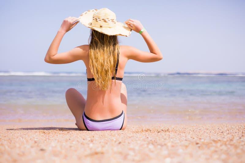 Mulher no biquini que descansa na praia no chapéu de palha Vocação do verão imagem de stock royalty free