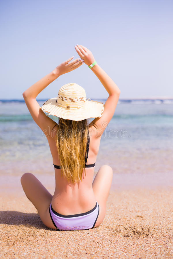 Mulher no biquini que descansa na praia no chapéu de palha Vocação do verão fotos de stock