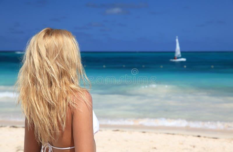 mulher no biquini que enjoing o dia na praia imagem de stock
