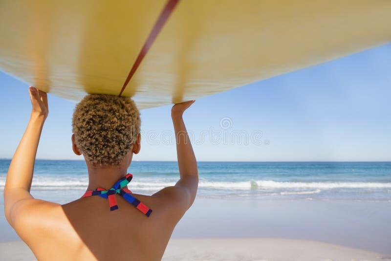 Mulher no biquini que leva a prancha em sua cabeça na praia na luz do sol foto de stock