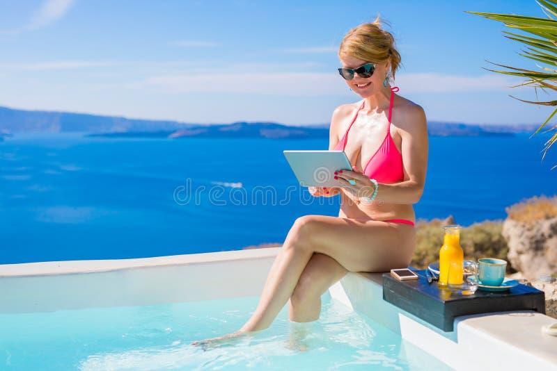 Mulher no biquini usando a tabuleta pela piscina fotos de stock