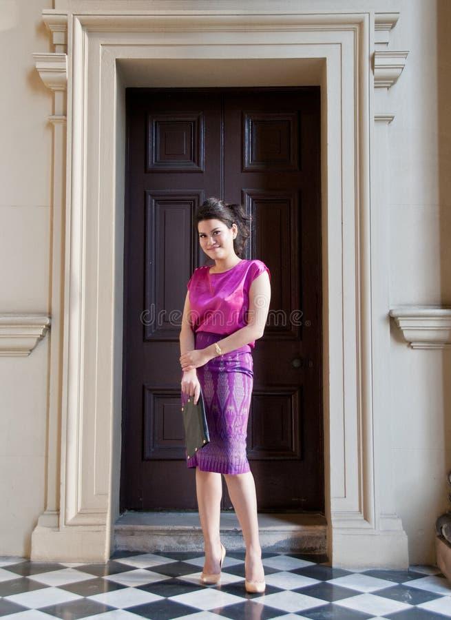 Mulher no bloco de notas tradicional de seda tailandês do negócio da posse do vestido fotografia de stock royalty free