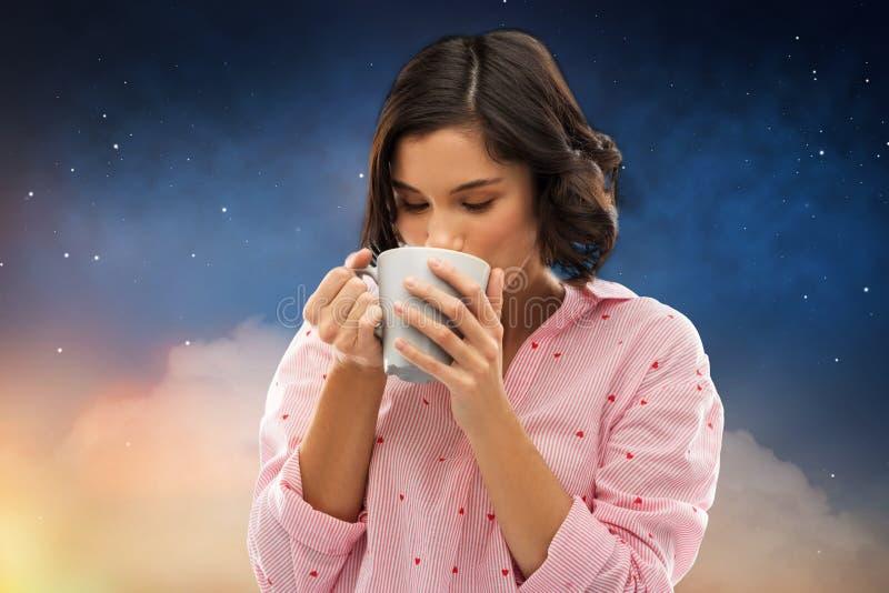 Mulher no café bebendo do pijama da caneca na noite imagem de stock royalty free
