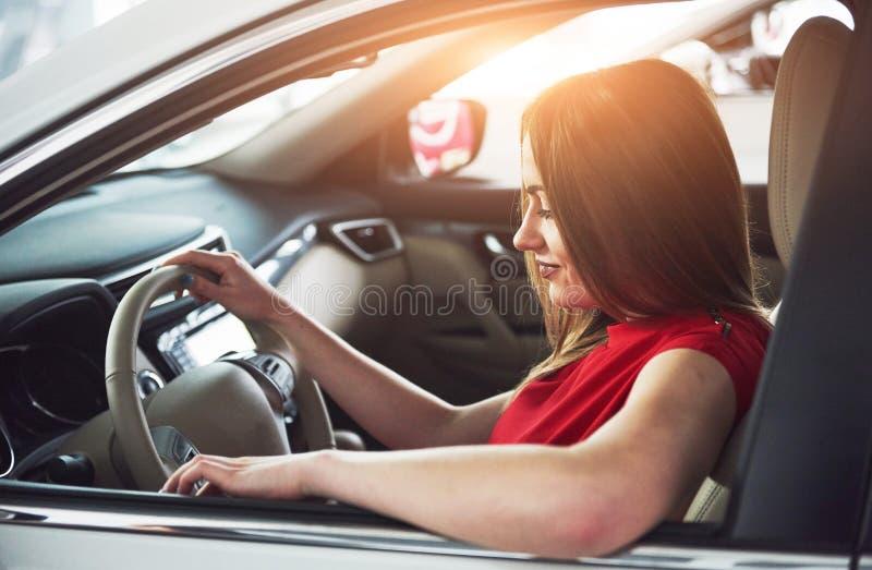 A mulher no carro interno mantém a roda girar em torno dos passageiros de vista de sorriso no taxista da ideia do banco traseiro  foto de stock
