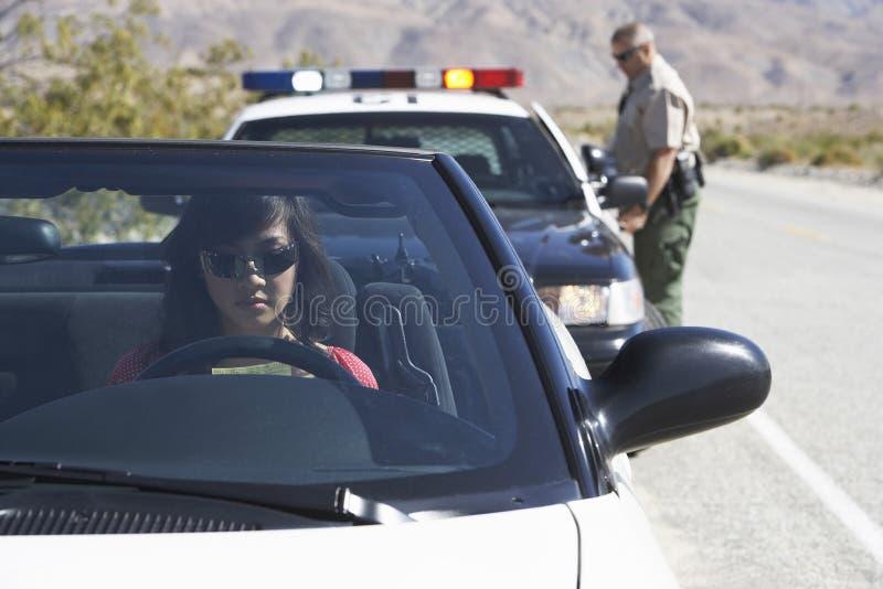 Mulher no carro que está sendo puxado sobre pelo agente da polícia fotos de stock royalty free