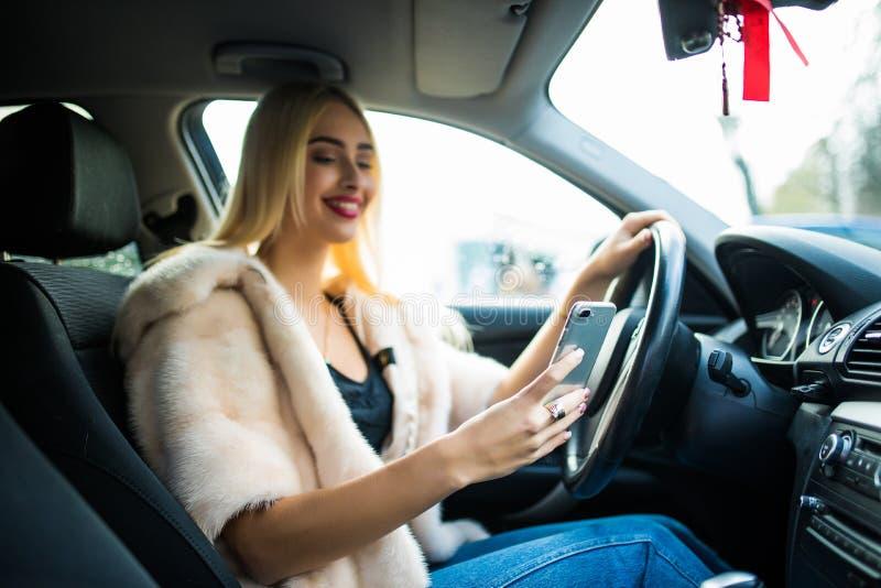 Mulher no carro que Texting no telefone celular enquanto conduzindo na cidade fotografia de stock