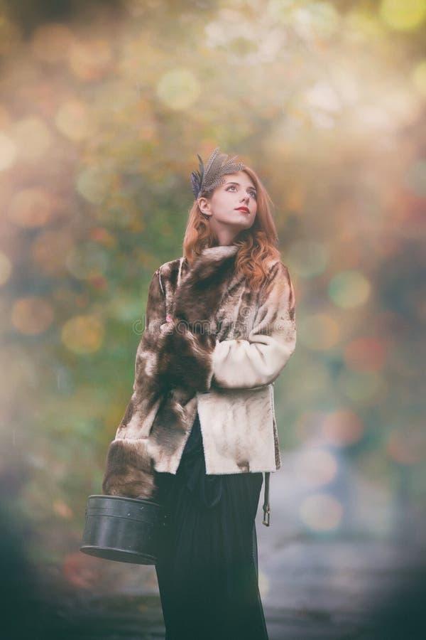 Mulher no casaco de pele com valise imagem de stock