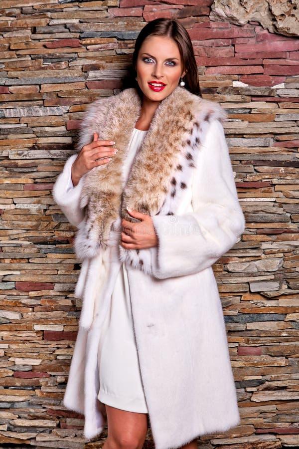 Mulher no casaco de pele luxuoso do lince imagem de stock