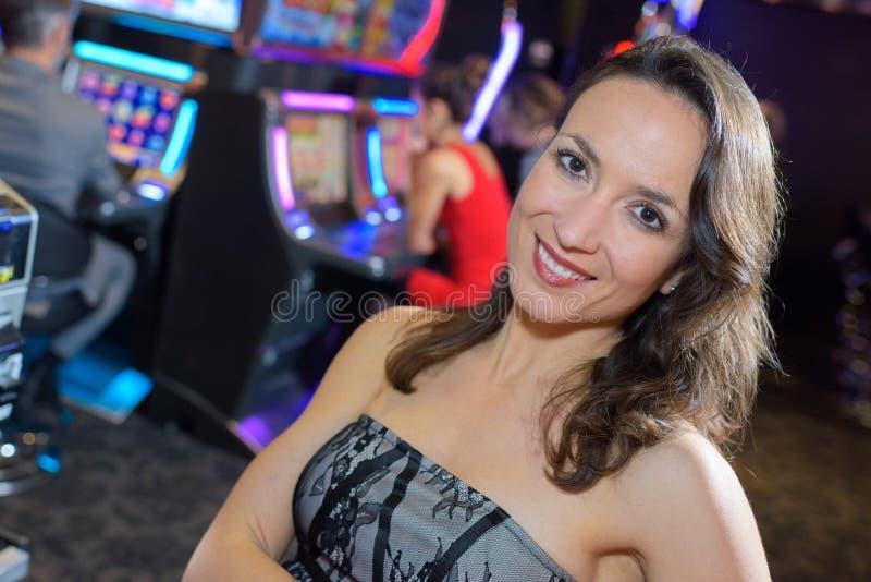 Mulher no casino ao lado do slot machine fotografia de stock royalty free