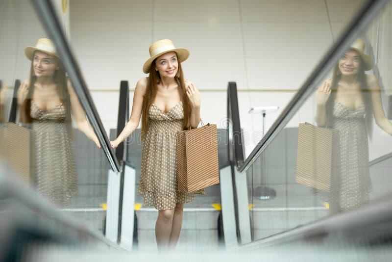Mulher no centro de compra que está na escada rolante foto de stock