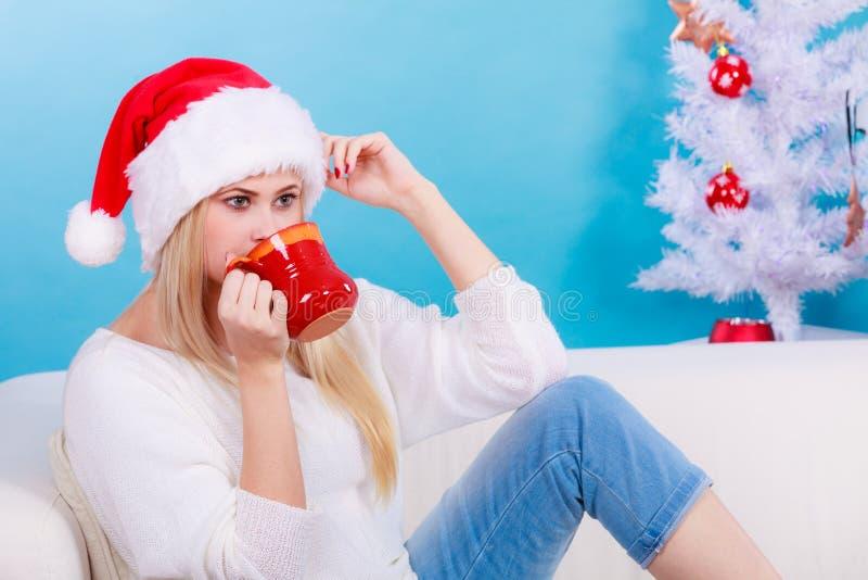 Mulher no ch? ou no caf? bebendo do chap?u do Natal de Santa imagem de stock royalty free