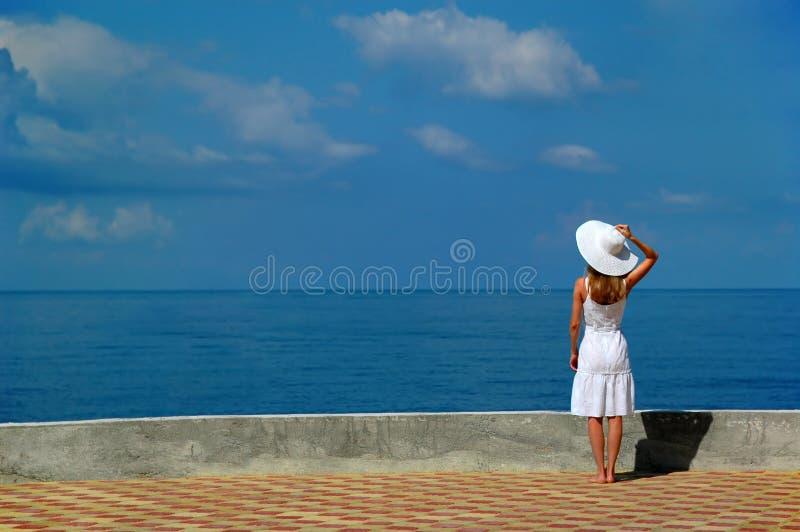 A mulher no chapéu branco olha o mar foto de stock
