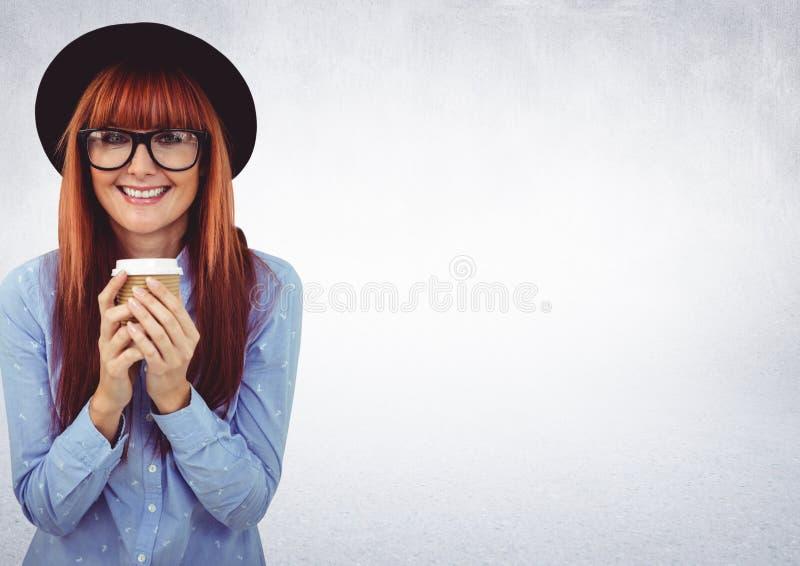 Mulher no chapéu com o copo de café contra a parede branca imagem de stock royalty free