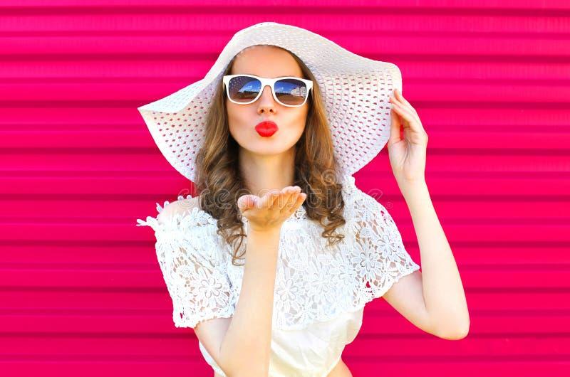 A mulher no chapéu de palha do verão envia um beijo do ar sobre o rosa colorido imagens de stock