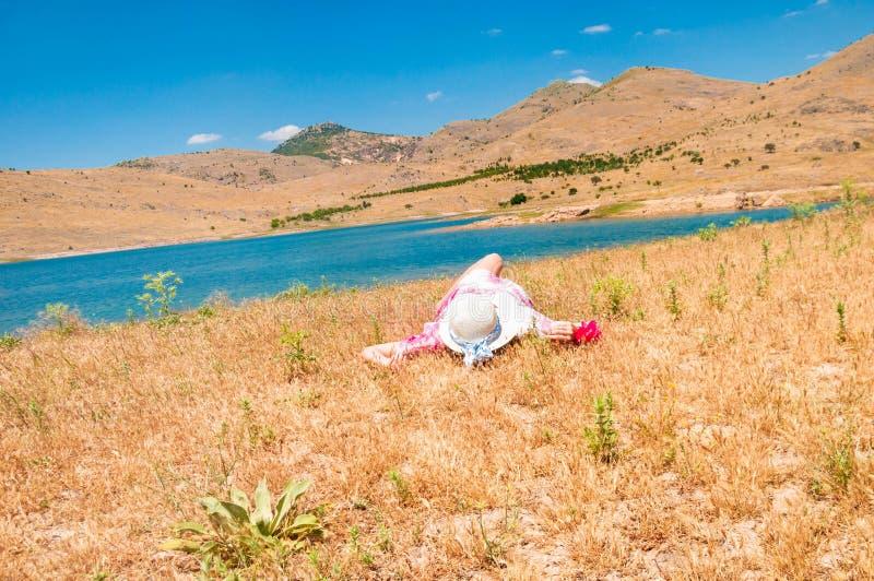 Mulher no chapéu de palha que encontra-se na grama seca fotografia de stock