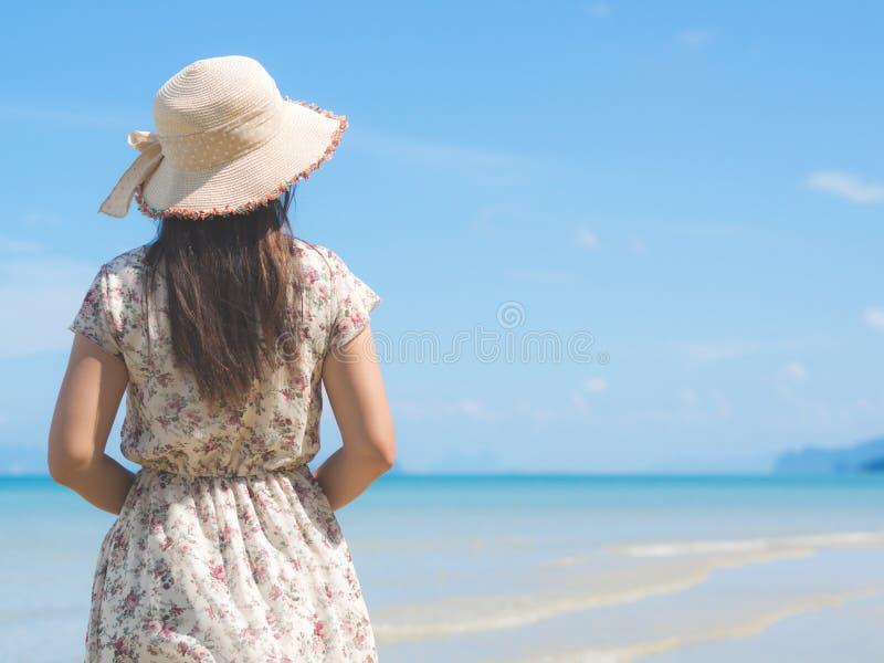 A mulher no chapéu de palha vestindo das férias de verão e a praia vestem a apreciação da vista no oceano foto de stock royalty free