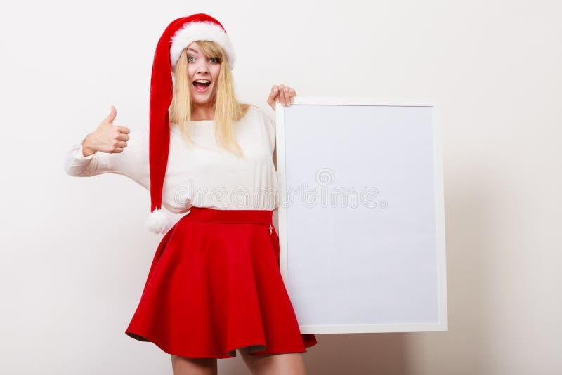 Mulher no chapéu de Santa com bandeira vazia Copie o espaço fotografia de stock
