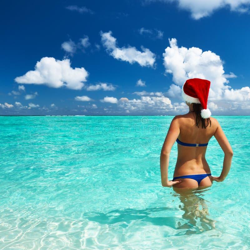 Mulher no chapéu de Santa na praia fotos de stock royalty free