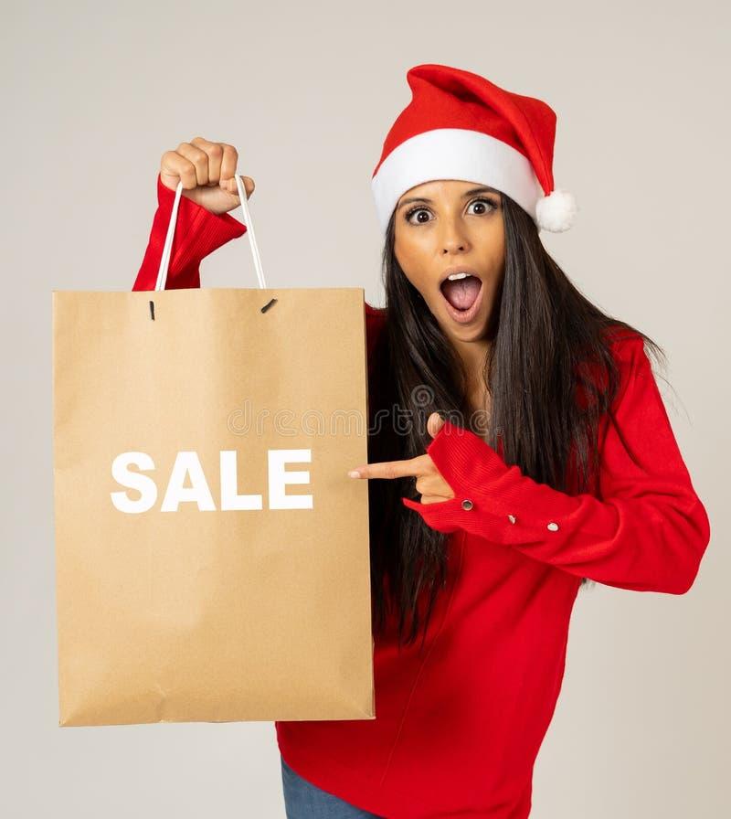 Mulher no chapéu de Santa que guarda o saco de compras do Natal com as vendas escritas nele que olha excitado e feliz foto de stock