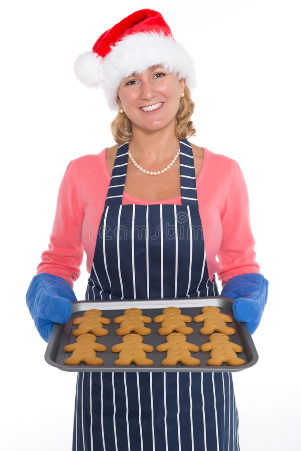 Mulher no chapéu de Santa que guarda uma bandeja de homens de pão-de-espécie foto de stock