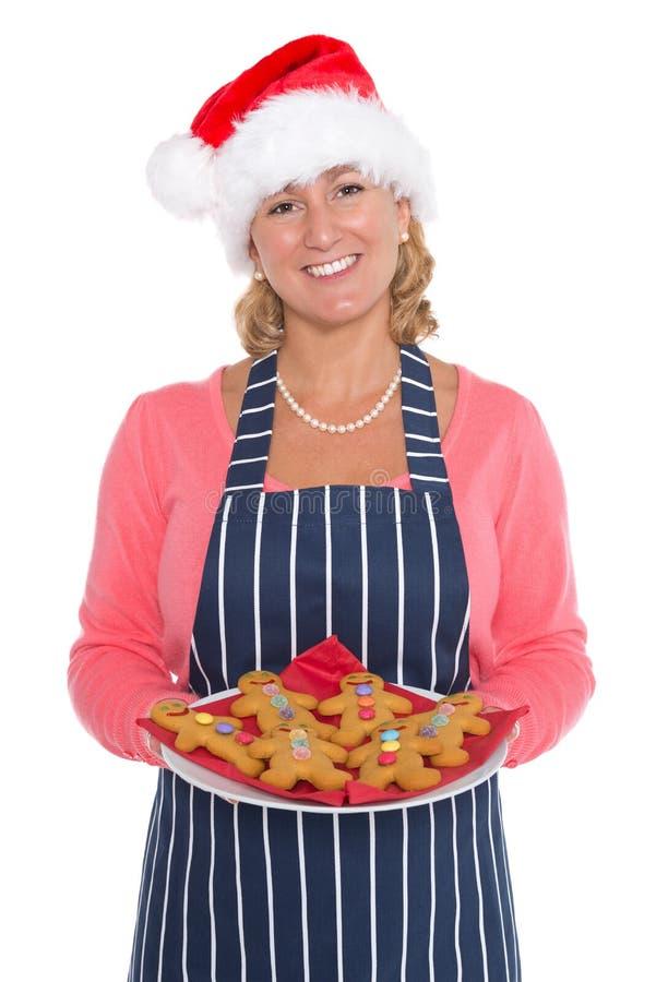 Mulher no chapéu de Santa que guardara uma placa de homens de pão-de-espécie foto de stock